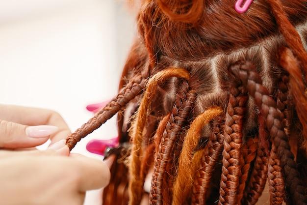 Schönheitssalon dienstleistungen hippie-stil frisur friseur hände zopf mädchen ingwer dreadlocks hell ... Premium Fotos