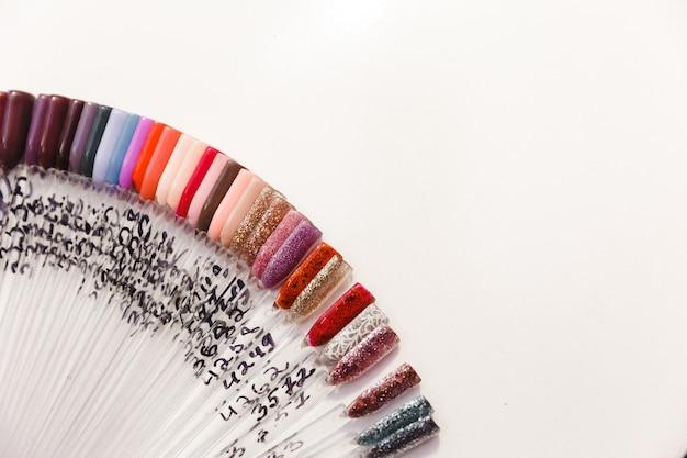 Schönheitssalon und maniküre-schrank, beispiele für gel-nagellacke. satz verschiedene nagellackfarben auf palette