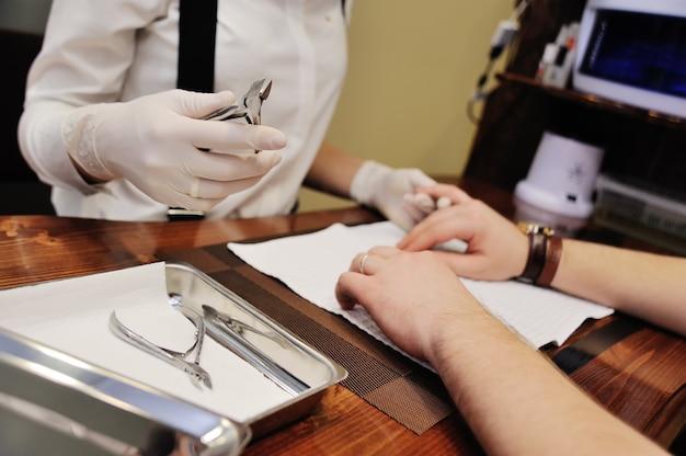 Schönheitssalonmeister macht eine maniküre zu einem männlichen kunden