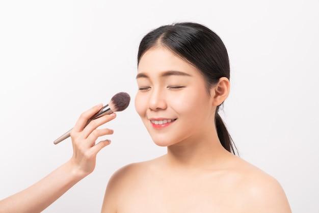 Schönheitsschuss der frau mit hand, die make-up-puderpinsel auf gesicht hält. kosmetik der perfekten haut.