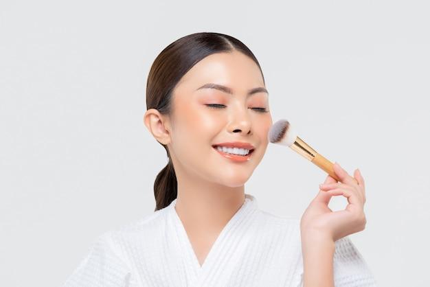 Schönheitsschuss der jungen asiatischen frau, die erröten auf ihrem gesicht anwendet