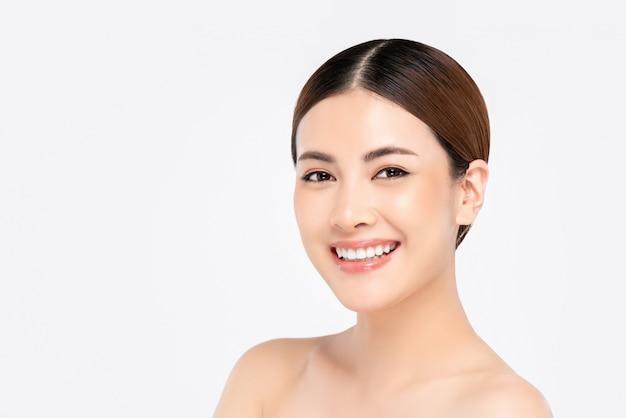 Schönheitsschuss der lächelnden schönen asiatischen frau lokalisiert auf weißer wand