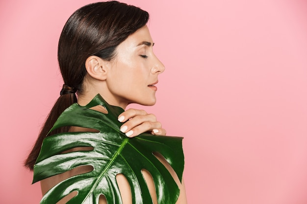 Schönheitsseitenansichtporträt einer attraktiven gesunden oben ohne brünetten frau lokalisiert, abdeckungen mit tropischem blatt