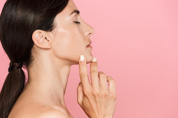 Schönheitsseitenansichtporträt einer attraktiven jungen topless-frau, die isoliert steht, die augen geschlossen