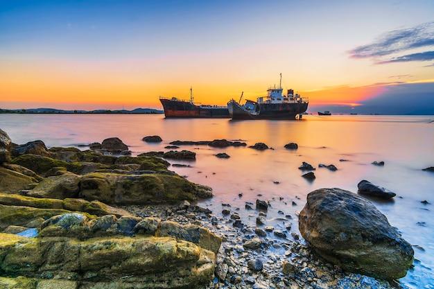 Schönheitssonnenuntergang und schiff am strand von tanjung pinggir