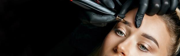 Schönheitsspezialist, der augenbrauenpuder-permanent-make-up auf weiblichen brauen tut. platz für text. negativer raum