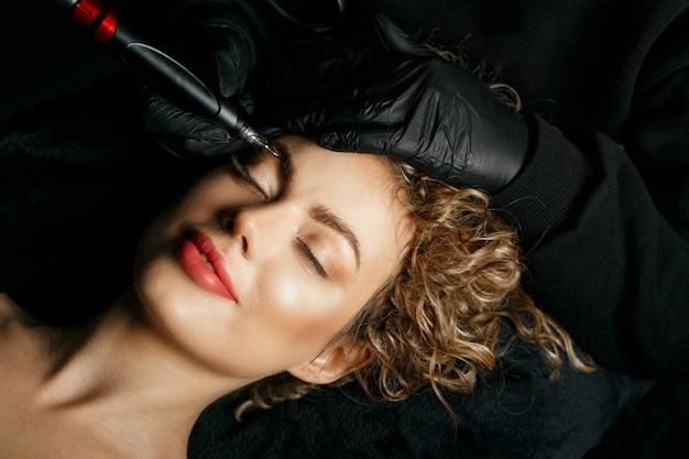 Schönheitsspezialist, der einer schönen jungen lockigen frau ein permanentes make-up mit brauenpuder aufträgt
