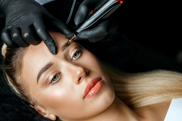 Schönheitsspezialisthand tut augenbrauen tätowieren auf weiblichen brauen