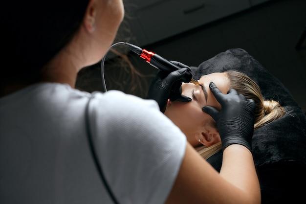 Schönheitsspezialistin für handschuhe, die einer schönen jungen frau permanentes augenbrauen-make-up auftragen