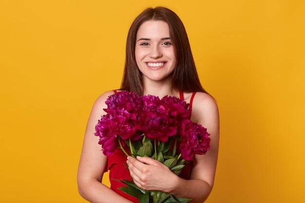 Schönheitsstudio-porträt der romantischen modellfrau mit burgunderfarbenen pfingstrosenblumen. attraktive frau, die mit zahnigem lächeln aufwirft