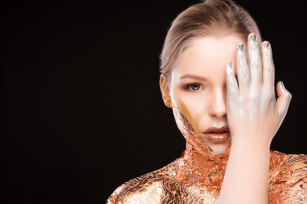 Schönheitsstudioporträt des blonden modells des glamours mit goldener glänzender folie auf ihren schultern. platz für text