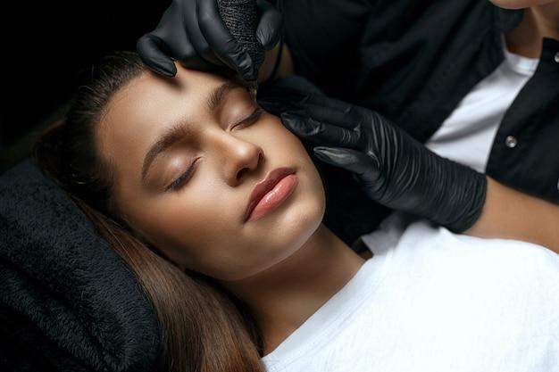 Schönheitsstylistin, die einer hübschen jungen frau ein permanentes augenbrauen-make-up im kosmetiksalon macht