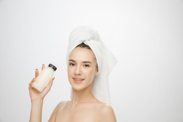 Schönheitstag. frau, die handtuch lokalisiert auf weißem studiohintergrund trägt. tag für selbstpflege, hautpflege, schönheitsroutine.