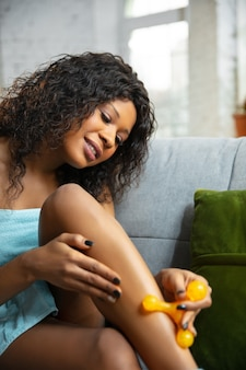 Schönheitstag. frau, die handtuch trägt, das ihre tägliche hautpflege-routine zu hause tut. auf dem sofa sitzen, die haut der beine mit der kosmetikrolle massieren und lächeln. konzept von schönheit, selbstpflege, kosmetik, jugend.