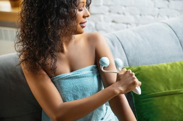 Schönheitstag. frau, die handtuch trägt, das ihre tägliche hautpflege-routine zu hause tut. auf dem sofa sitzen, die haut der hände mit der kosmetikrolle massieren und lächeln. konzept von schönheit, selbstpflege, kosmetik, jugend. Kostenlose Fotos