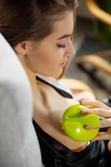 Schönheitstag. frau, die seidengewand trägt, das ihre tägliche hautpflege-routine zu hause tut. auf dem sofa sitzen, die nackenhaut mit der kosmetikrolle massieren und lächeln. konzept von schönheit, selbstpflege, kosmetik, jugend.