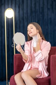 Schönheitstag. junge frau in rosa dessous und mit bändern am hals, die in den spiegel schauen