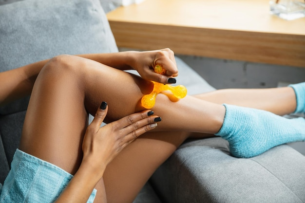 Schönheitstag. nahaufnahme der frau, die handtuch trägt, die ihre tägliche hautpflege zu hause tut. auf dem sofa sitzen und die haut der beine mit der kosmetikrolle massieren.