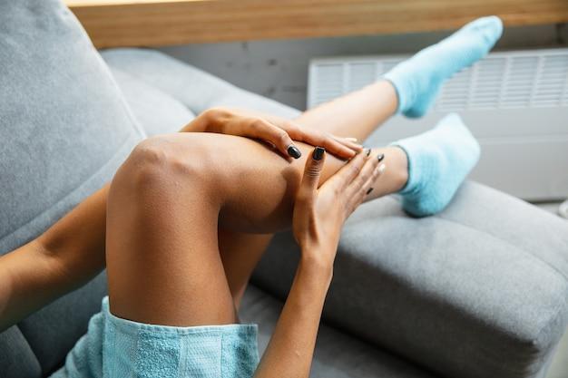Schönheitstag. nahaufnahme der frau im handtuch, die ihre tägliche hautpflege zu hause tut. auf dem sofa sitzen, massieren und feuchtigkeitscreme auf die beinhaut auftragen. konzept von schönheit, selbstpflege, kosmetik, jugend.