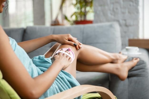 Schönheitstag. schließen sie oben von der afroamerikanerfrau im handtuch, die ihre tägliche schönheitsroutine zu hause tut. sie saß auf dem sofa und massierte die haut ihrer beine. konzept von schönheit, selbstpflege, kosmetik, gesundem lebensstil.