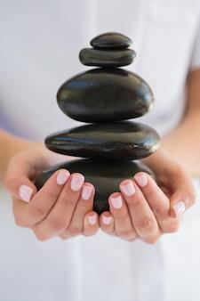 Schönheitstherapeut, der stapel von steinen für massage hält