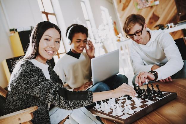 Schöpfer der jungen leute, die schach im coworking-platz spielen