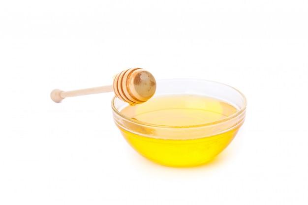 Schöpflöffel und honig in der glasschale lokalisiert auf weiß
