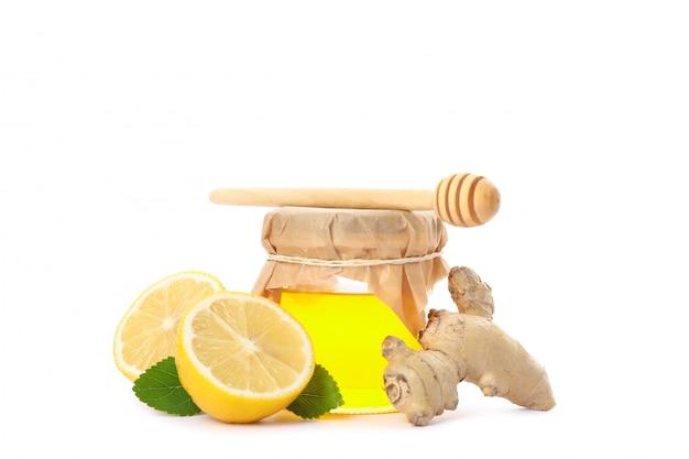 Schöpflöffel, zitronen, ingwer und glas mit honig lokalisiert auf weiß