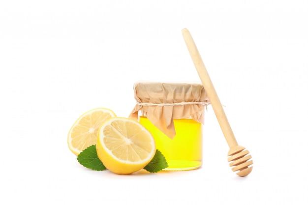 Schöpflöffel, zitronen und glas mit honig lokalisiert auf weiß