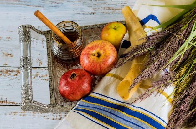 Schofar, honig, apfel und granatapfel über holztisch.