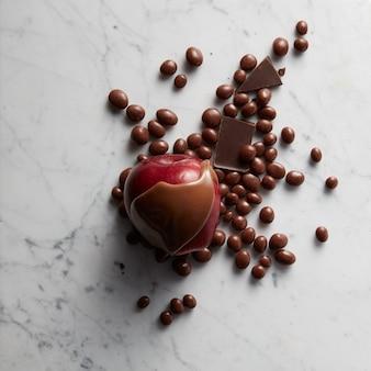 Schokolade auf roten apfelfrüchten und süßigkeiten auf weißer marmoroberfläche