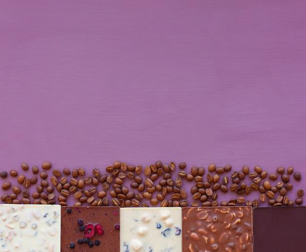 Schokolade auf veilchen mit kaffeebohnen. schokolade. schokoladentafel. nussschokolade. kopieren sie platz.