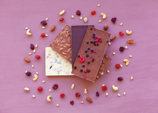 Schokolade auf veilchen, umgeben von nüssen und trockenfrüchten. schokolade. schokoladentafel.