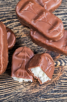 Schokolade aus kakao, zucker und milchpulver, nahaufnahme von schokoladenprodukten aus kakao und anderen zutaten mit einer weißen kokosnussfüllung