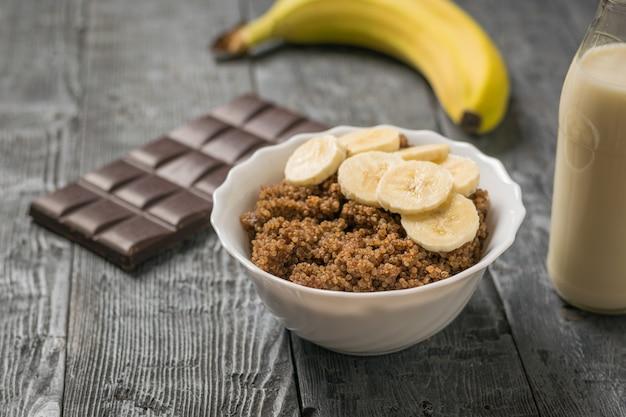 Schokolade, banane und eine schüssel quinoa-brei auf einem schwarzen holztisch. gesunde ernährung.