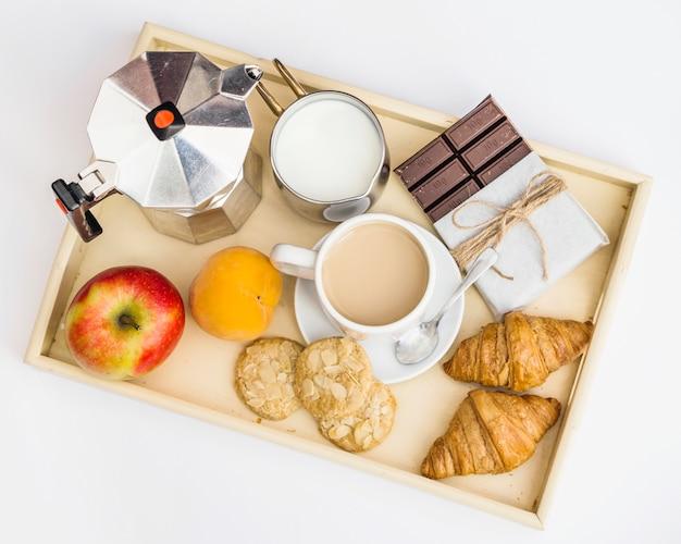 Schokolade, croissant, apfel, kekse, milch und tee zum frühstück