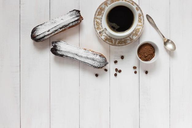 Schokolade eclairs und kaffee auf einem hölzernen hintergrund