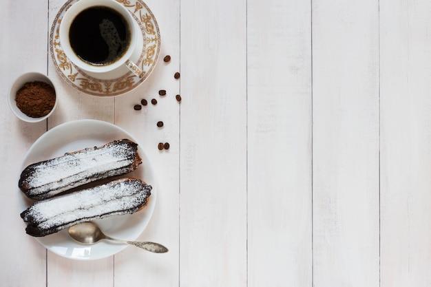 Schokolade eclairs und kaffeebohnen auf einem hölzernen hintergrund