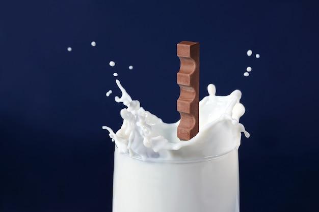Schokolade fällt in milch auf blauem hintergrund
