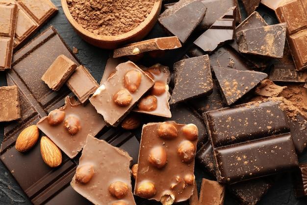 Schokolade, geschmolzene schokolade und mandel auf schwarzem hintergrund