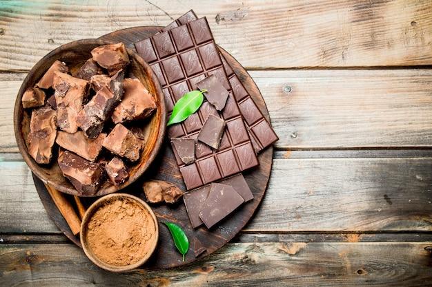 Schokolade in einer schüssel mit kakaopulver auf dem brett. auf einem hölzernen hintergrund.
