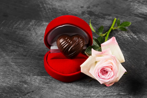 Schokolade in form von herzen in einem roten kasten für einen ring, eine rosa rose auf einem dunklen hintergrund. konzept liebe zur schokolade