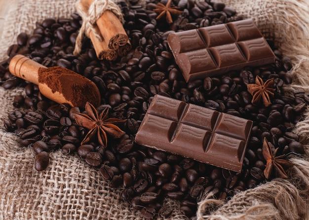 Schokolade, kaffeebohnen, anis auf hölzernem hintergrund