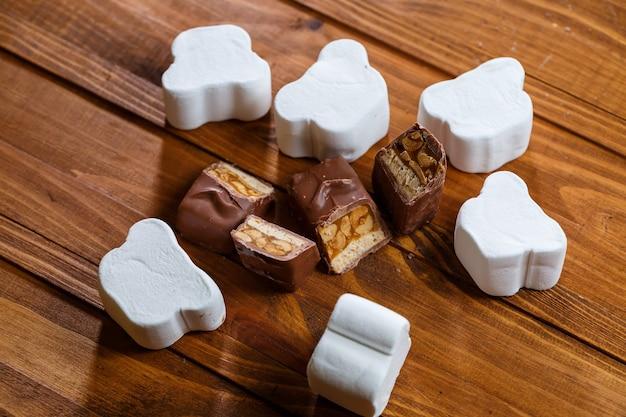 Schokolade mit nüssen auf einem holzbrett mit marshmallows