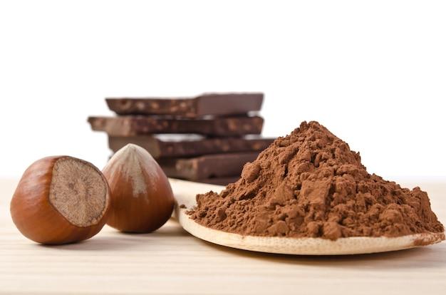 Schokolade mit nüssen und kakaopulver im holzlöffel auf holztisch