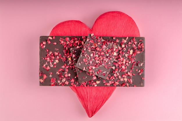 Schokolade mit stücken getrockneten beeren liegt ein stapel auf rotem herzen