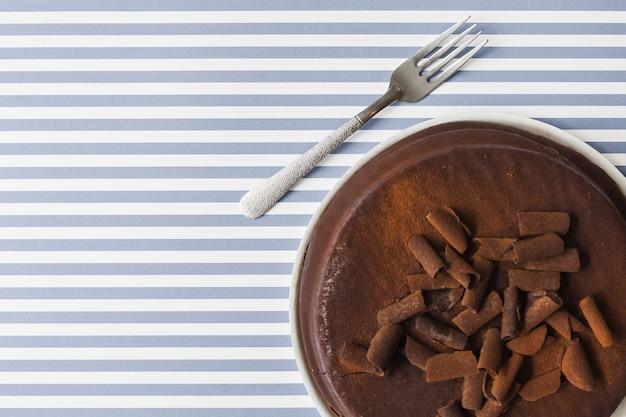 Schokolade reibt beläge auf gebackenem kuchen über dem streifenhintergrund