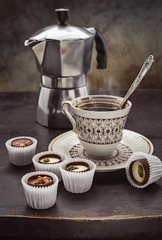 Schokolade süßt eine tasse duftenden kaffee und eine kaffeekanne auf einem dunklen holztisch