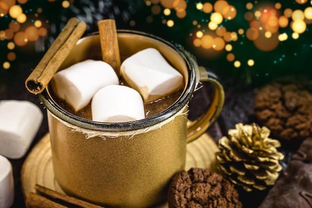 Schokolade und heißer kakao mit marshmallow in einem goldenen keramikbecher, umgeben von weihnachtssachen auf einem rustikalen holztisch. das konzept der gemütlichen feiertage und neujahr und weihnachten.