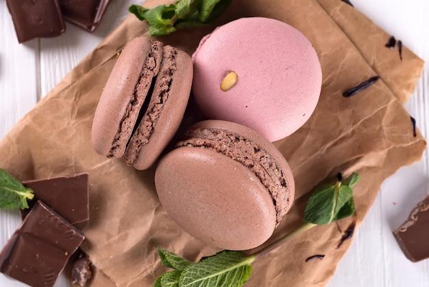 Schokolade und makronen auf altem küchentisch. draufsicht